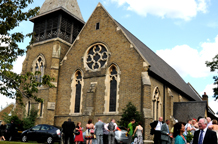 Wedding photograph of a popular and welcoming London wedding venue Christ Church Colliers Wood built in the rural Gothic style and hit by a bomb in the Second World War