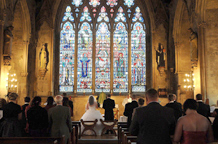 The wonderfully colourful stained glass window in this wedding photograph taken at the ancient and historic 13th Century London wedding venue St Etheldreda's in Ely Place