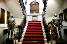 A wedding picture of the historic suits of armour that flank the entrance at the base of the grand staircase at the unique London wedding venue the Armourers' Hall